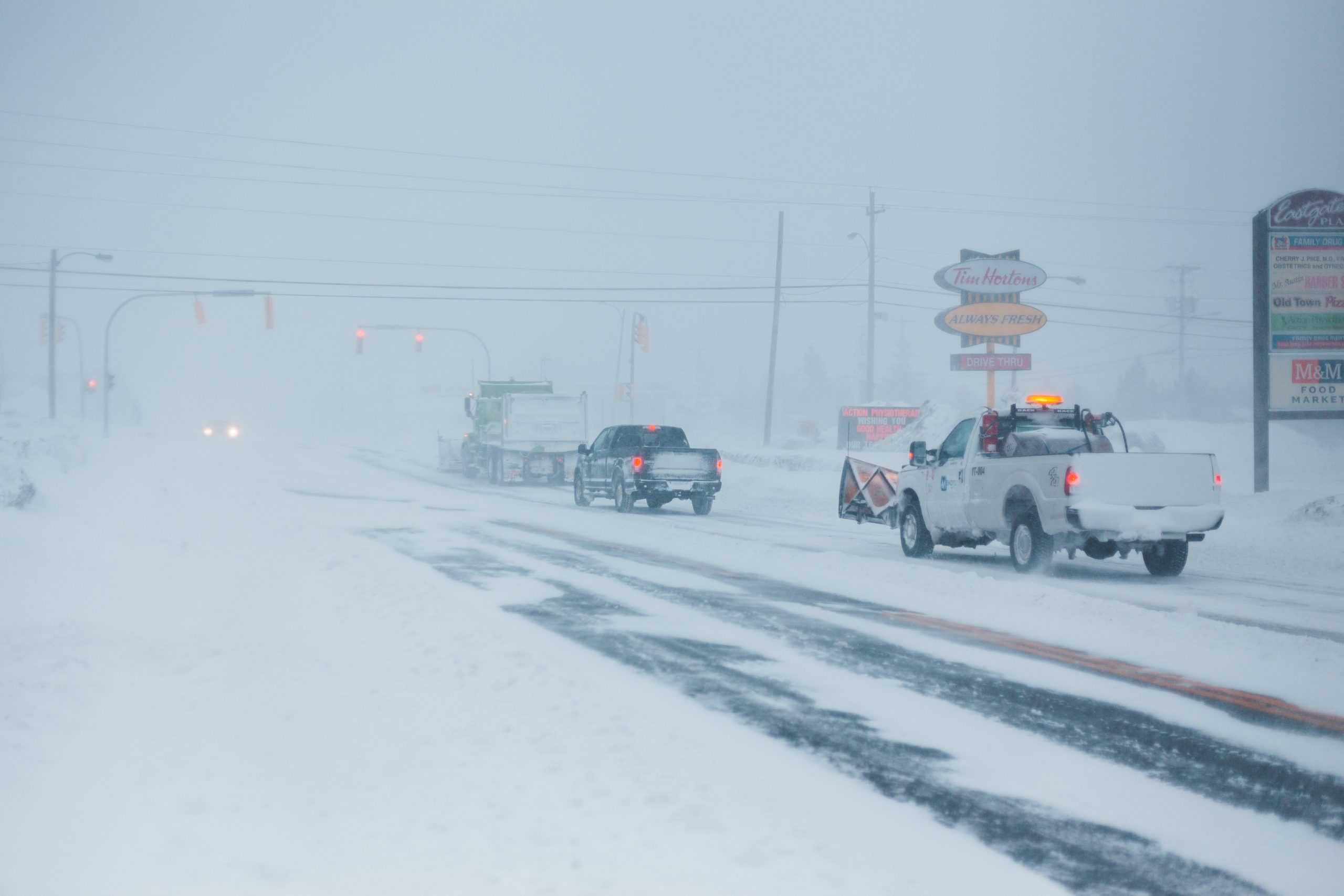 Cars drive carefully in the snow to avoid auto body repairs.