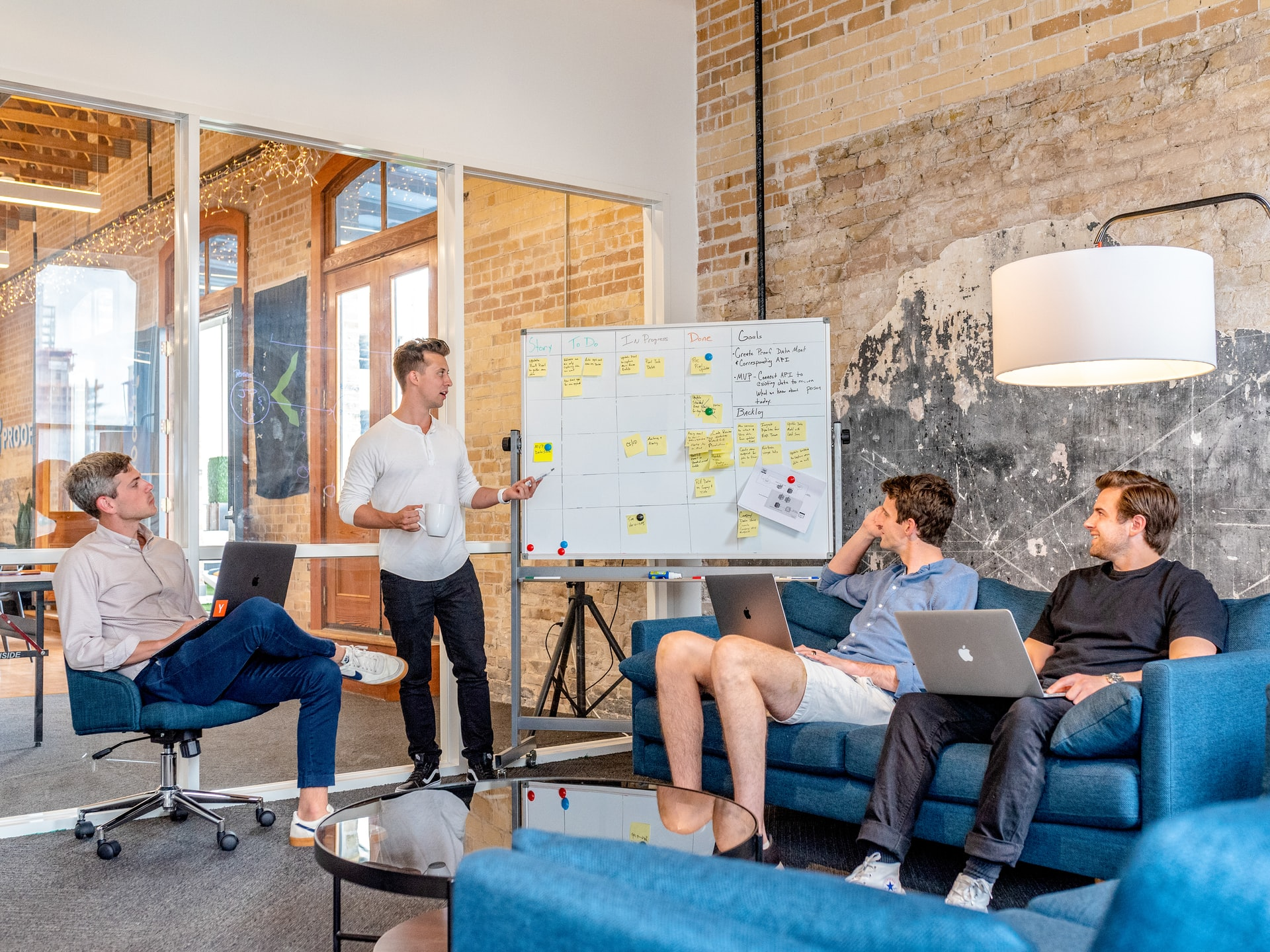 several businessmen sitting a room working on a business plan at a whiteboard